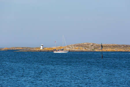 sea mark: Sailboat at the rocky coast with lighthouse and seamark Stock Photo