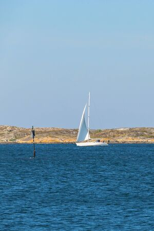 sailingboat: Sailing in a rocky coastline at summer