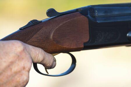 finger on trigger: Finger on the trigger of a shotgun