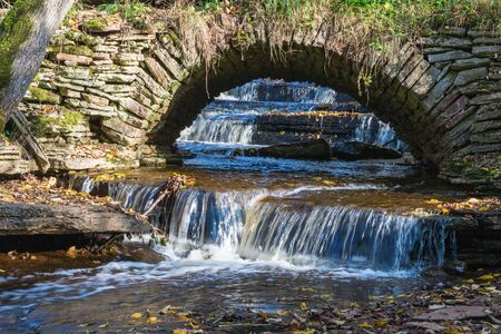 old bridge: Old arched bridge with waterfall