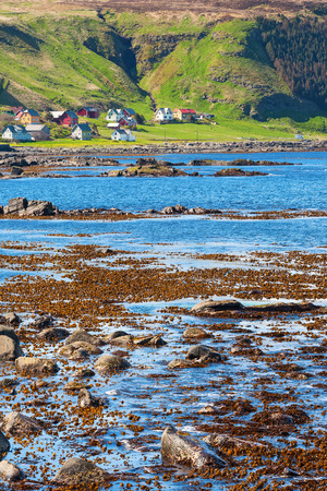 wrack: Beach with seaweed and the coastal village
