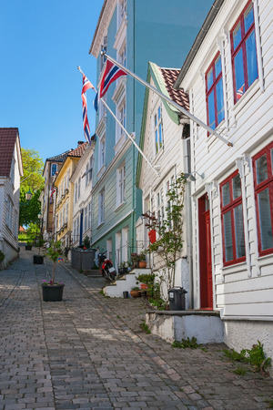 residential idyll: Alley with old wooden houses and Norwegian flags in Bergen