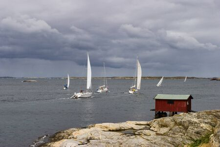 thundercloud: Sailing boats at the coast and storm clouds Stock Photo