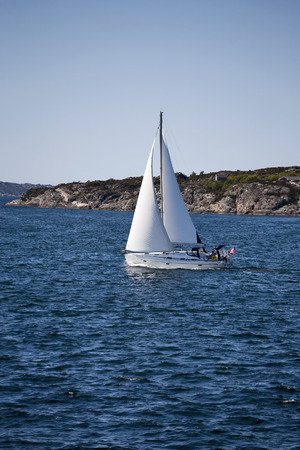 waterscapes: Sailboat and rocky coastline Stock Photo