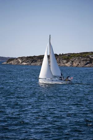 sailingboat: Sailboat and rocky coastline Stock Photo