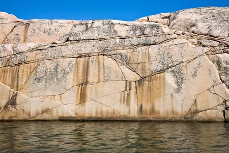 the edge: Granite rocks at the waters edge Stock Photo