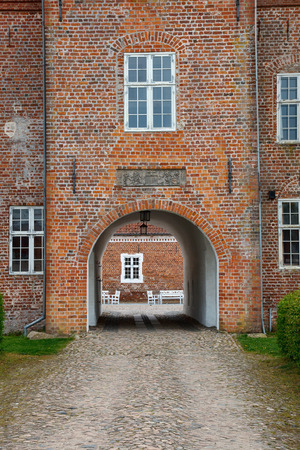 brownstone: Entrance through an archway into a castle Editorial