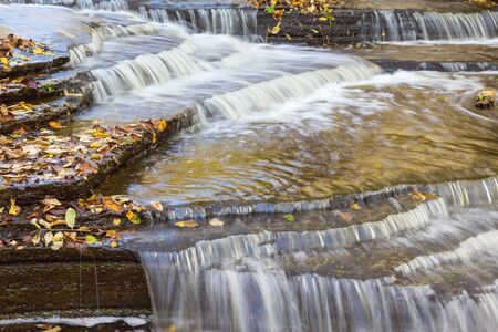 no rush: Waterfall with autumn leaves on slated stone in in the creek