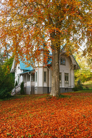 Wooden house with autumn colors in the garden Stock Photo
