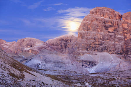 alpenglow: Moonrise over the dolomites mountains in alpenglow Stock Photo