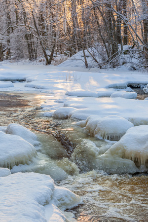 River flowing through the forest with snow and ice