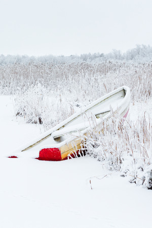 rowing boat: Red rowing boat on the beach in the reed with snow