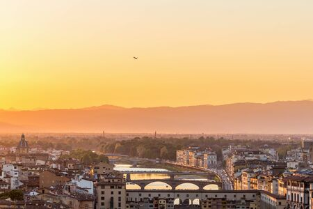Sunset view of Florence in Italy with a airliner that lifts