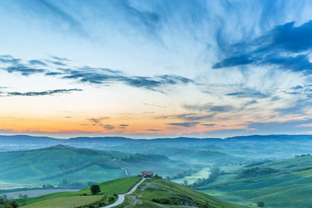 Valleys and hills in a hilly landscape at sunrise Stock Photo