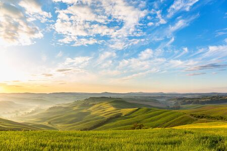 Sunrise in the rolling rural landscape with fog in the valley Stock Photo