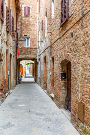 Empty alley with old brick houses Stock Photo