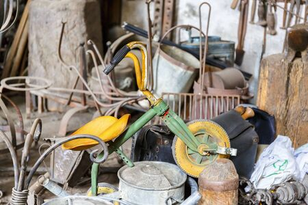 Old tricycle for children in a metal piece of junk