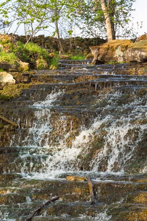 Waterfall with a creek in a pasture in the spring Stock Photo