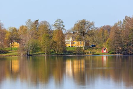 waterfront property: Houses on the hill by the lake in the spring Stock Photo