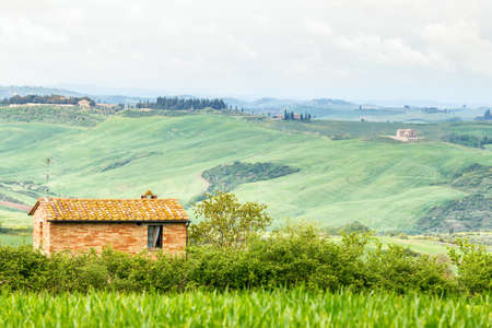 Rural Italian landscape with a small cottage at a valley Stock Photo