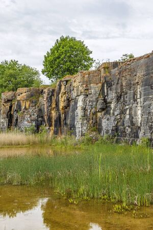 rock formation: Rock Wall by a pond in an old abandoned mine Stock Photo