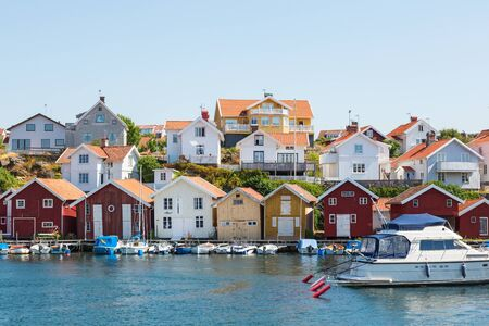 Boats at the jetty with boat houses in a coastal settlement on the Swedish west coast