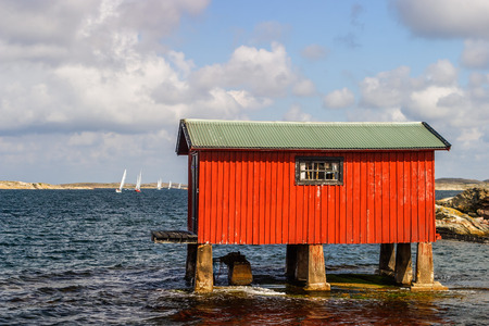Red boathouse by the sea Stock Photo