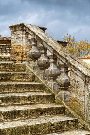 Old ornate stone stair with dark rain clouds Фото со стока