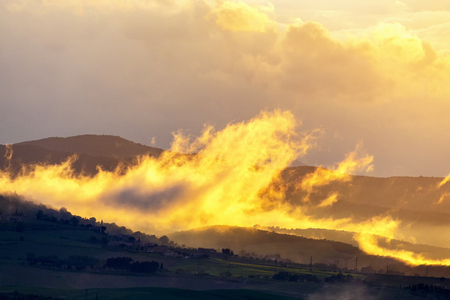 Low clouds over a rolling landscape at sunset