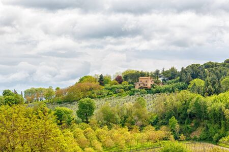 Fruit tree cultivation with a farmhouse in Tuscany Stock Photo