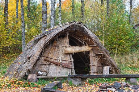 Stenen tijdperk hut van riet in het bos Stockfoto
