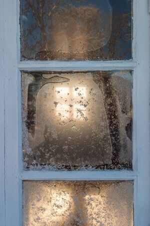 Frosty window with sunlight in winter