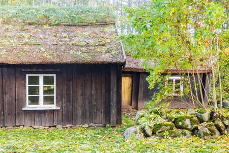 Old wooden cottage with thatched roof