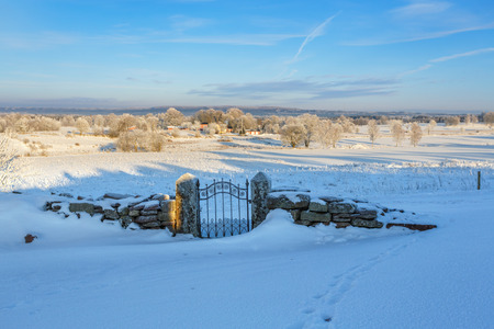Snowy rural landscape with a snow covered gate