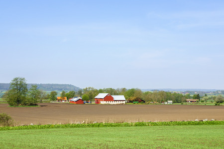 Landscape view with fields and farms in the swedish countryside in spring Archivio Fotografico