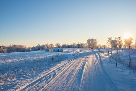 Snowy road in sunset at a beautiful country landscape Imagens