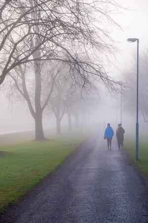 Women walking on a walkway in autumn fog