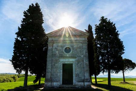 Cappella di vitaleta in the sun backlighting on a hill in the countryside