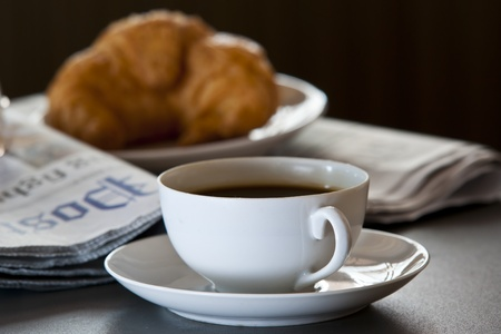 Fresh-baked croissant, Hot coffee and newspaper. reading glasses. Focus on cup.