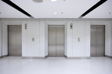 Three elevator doors in corridor of office building  photo