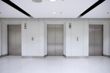 elevators: Three elevator doors in corridor of office building
