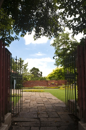 The iron gate entrance to peaceful flower garden photo