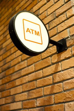 subsidize: Circle shape ATM sign on brick wall