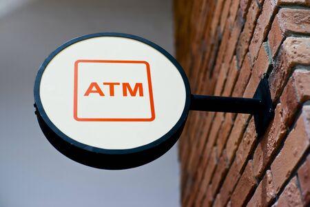 subsidize: Circle shape ATM sign on brick wall