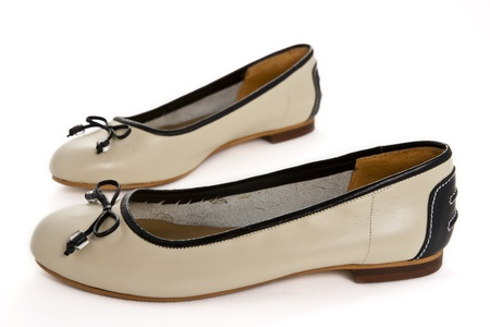 Pair of beige female shoes with black bow over white background  photo