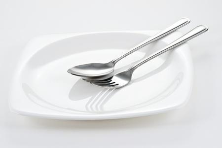 cuchara: Tenedor y cuchara en un plato blanco