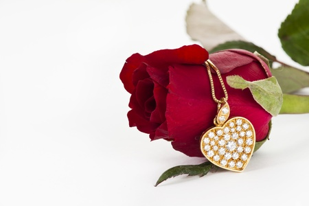 Heart pendant with diamond and red rose on white background photo