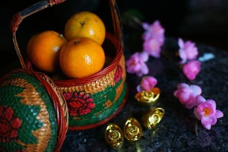 Cesto di mele e arance con lingotti d'oro e fiori di prugna