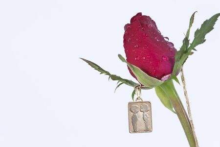 The picture of lovers kissing on Gold pendant with red rose photo
