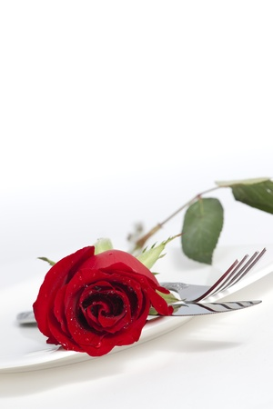 Valentine Series, Red rose and cutlery on white plate Stockfoto